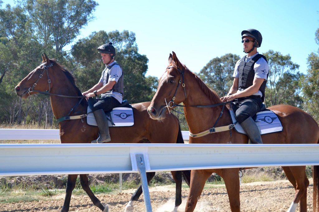 2 jockeys riding racehorses.